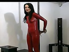 Fastened up brunette cutie in red latex and high heels enjoys posing in front of the livecam