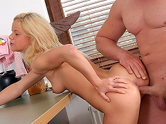 A blonde teenage cutie is sitting on top of a desk. A guy who is next...