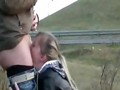 Golden-haired is on her knees engulfing his wang on the side of the road