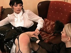 Sexy tow-haired and gloominess dommes spank and fuck a hot tranny's ass